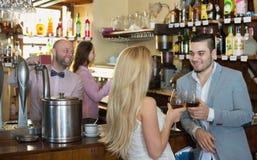 Par som dricker vin på stången Royaltyfria Bilder