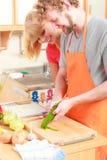 Par som förbereder gurkan för grönsaksalladskalning Arkivbild