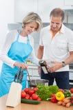 Par som förbereder mat i kök Arkivfoto