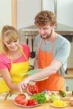 Par som förbereder matsallad för nya grönsaker Royaltyfria Bilder