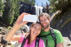 Par som fotvandrar ta smartphoneselfie i Yosemite Royaltyfri Bild