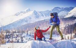Par som fotvandrar utanför i vinternatur Royaltyfri Bild