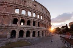 Par som går nära Colosseumen på solnedgången Royaltyfri Foto