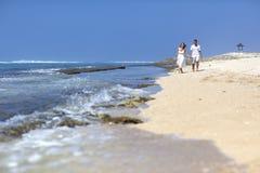 Par som går på den idylliska stranden Arkivfoto