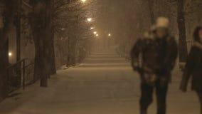 Par som går på natten i snöstormen lager videofilmer