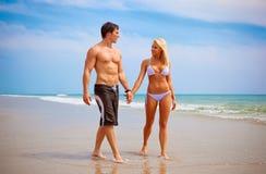 Par som går på stranden arkivfoto