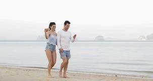 Par som går på stranden genom att använda cellSmart telefoner som tar Selfie innehavhänder, kvinnaturister för ung man som direkt
