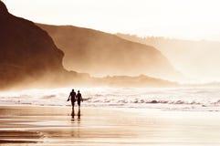 Par som går på stranden med dimma royaltyfri foto