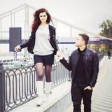 Par som går rymma händer utomhus Han stöttar henne, medan hon går på balustraden Arkivfoton