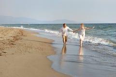 Par som går rymma tillsammans händer på stranden nära havet royaltyfri foto