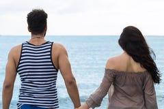 Par som går sommarsemester, den härliga unga lyckliga mannen för folk och tillbaka bakre sikt för kvinna Royaltyfri Fotografi