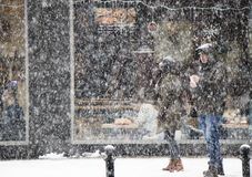 Par som går stadsgatan i tungt snöfall och folk som bakom äter i ett restaurangfönster royaltyfria bilder
