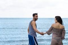 Par som går strandsommarsemester, den härliga unga lyckliga mannen för folk och kvinnaleende Royaltyfri Foto