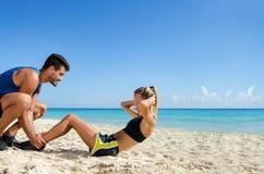 Par som gör ab-knastrande på stranden Arkivfoto