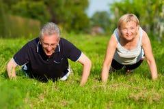 par som gör den mogna pushupssporten fotografering för bildbyråer