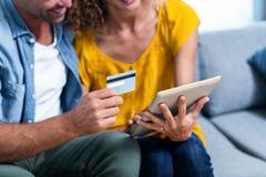 Par som gör online-shopping på den digitala minnestavlan Arkivbild