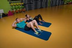 Par som gör Sitta-UPS den buk- knastrandet Royaltyfri Foto