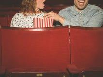 Par som håller ögonen på en film i en filmbiograf Royaltyfri Foto