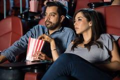 Par som håller ögonen på en film och äter popcorn arkivfoto