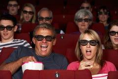 Par som håller ögonen på filmen 3D i bio Fotografering för Bildbyråer