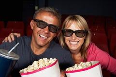 Par som håller ögonen på filmen 3D i bio royaltyfri foto