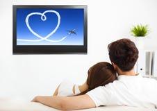 par som håller ögonen på TV-program i vardagsrum royaltyfri bild