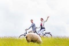 Par som har cykeln för havskusten, turnerar på flodfördämningen Royaltyfria Foton