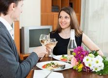 Par som har den romantiska matställen med champagne Arkivbild