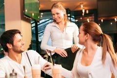 Par som har en goda i kafé royaltyfria foton