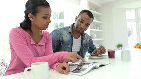 Par som har frukosten och den läs- tidskriften i kök stock video