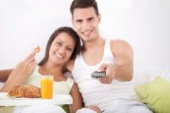Par som har frukosten och håller ögonen på TV Royaltyfri Fotografi