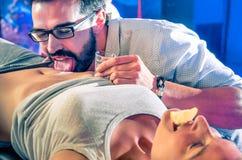 Par som har gyckel i diskonattklubb med kropptequilapartiet Royaltyfria Bilder