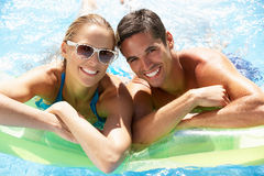 Par som har gyckel i simbassäng Fotografering för Bildbyråer