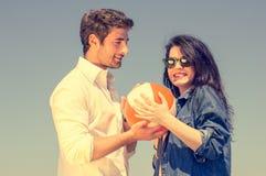 Par som har gyckel med en strandboll arkivbilder