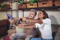 Par som har gyckel, medan spela videospel Royaltyfri Fotografi