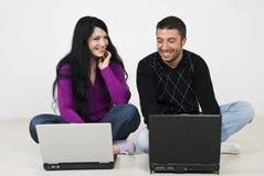 Par som har gyckel på bärbar dator Fotografering för Bildbyråer
