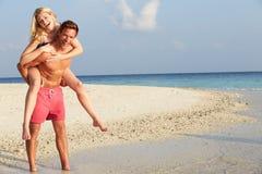 Par som har gyckel på tropisk strandferie Royaltyfri Bild