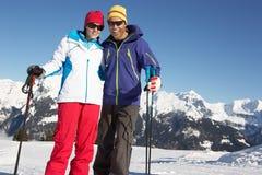 Par som har gyckel skidar på, ferie i berg Royaltyfri Bild