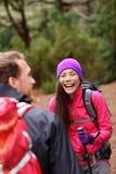 Par som har gyckel som skrattar att fotvandra i skog Royaltyfri Fotografi