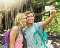 Par som har gyckel som tillsammans tar bilder utomhus på vandring Royaltyfri Fotografi