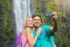Par som har gyckel som tillsammans tar bilder utomhus på vandring Royaltyfria Bilder