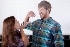 Par som har gyckel under matlagning royaltyfri foto