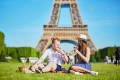 Par som har picknicken nära Eiffeltorn i Paris, Frankrike Arkivbild