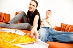 Par som har pizza på soffan Arkivbilder