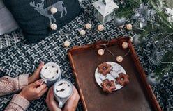 Par som har varm choklad under julgranen arkivbild