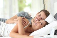 Par som hemma flörtar på en säng fotografering för bildbyråer