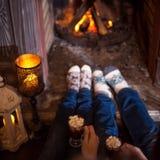 Par som hemma kopplar av att dricka kakao Foten i ull slår nära spisen Begrepp för vinterferie royaltyfri fotografi