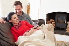 Par som hemma kopplar av att dricka vin Fotografering för Bildbyråer