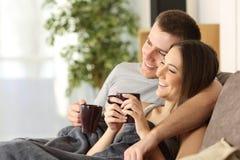 Par som hemma kopplar av och dricker kaffe fotografering för bildbyråer