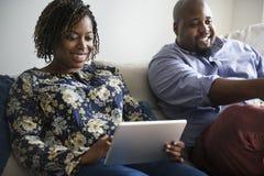 Par som hemma kopplar av på en soffa arkivbilder